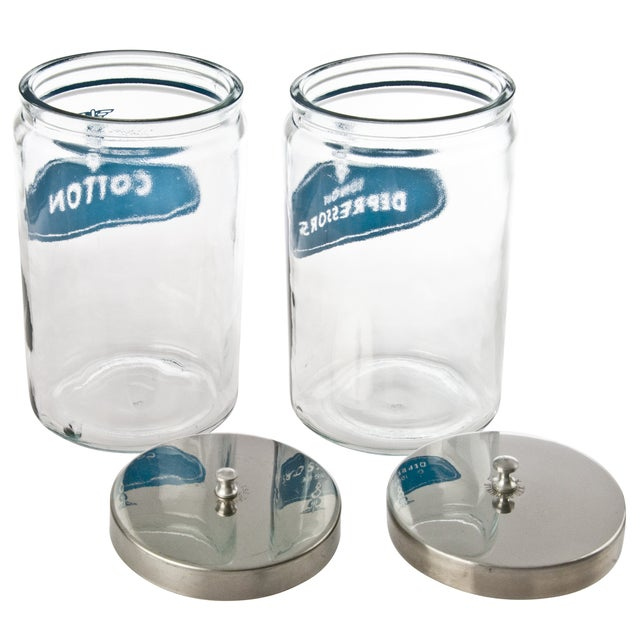 """We love the industrial, pharmacy feel of these vintage, glass medical storage jars with aluminum lids. One marked """"Tongue..."""