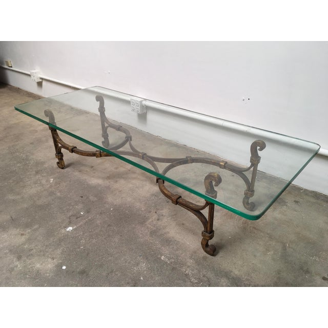 Gilded iron coffee table attributed to Arturo Pani. Gorgeous C-Scroll legs and elegant belt banded iron make up the...