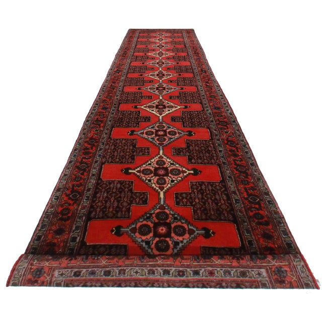 Offered is this vintage Persian Seneh runner. Hand-knotted from wool. Features a rich red floral design.