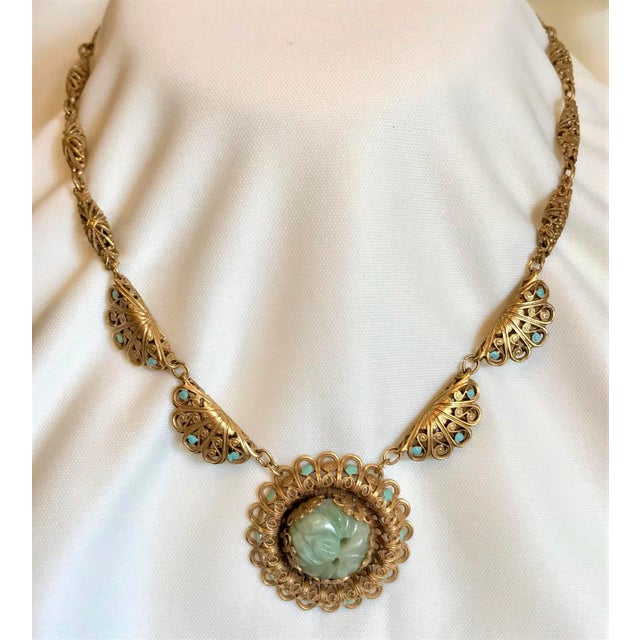 Circa 1930s ornate filigree design brass link necklace embellished with aqua blue enameling and set with round, carved...