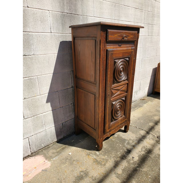 Antique 19th century small bonnetiere featuring a drawer above a single door adorned with geometrical raised panels with...