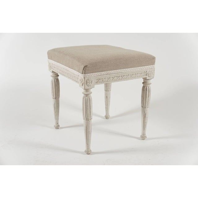 A near pair of circa 1790, Swedish Gustavian period wood stools in original paint having upholstered seats above carved...