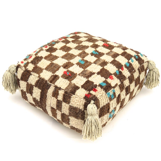 Moroccan floor pouf made from a vintage Berber rug handwoven with ivory, red, and blue colored hand spun wool. The bottom...