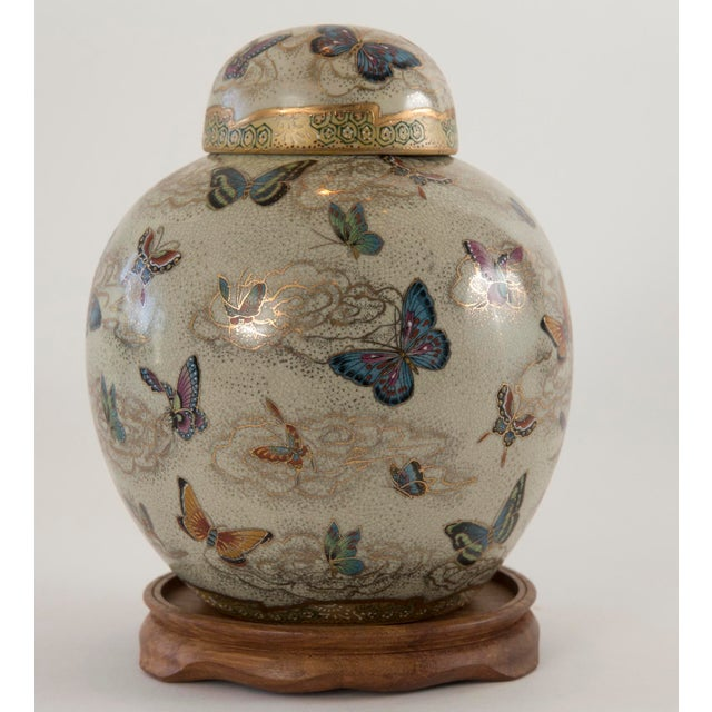 A vintage Japanese Satsuma butterfly ginger jar with lid on carved wooden base. The jar is hand-painted overglaze...