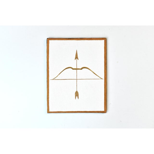A contemporary painting in gold gilt of a bow and arrow, on canvas board.