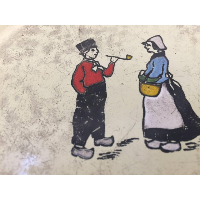 Vintage French pressed square metal enameled trivet with a couple in Britain traditional costumes West of France. Ivory...