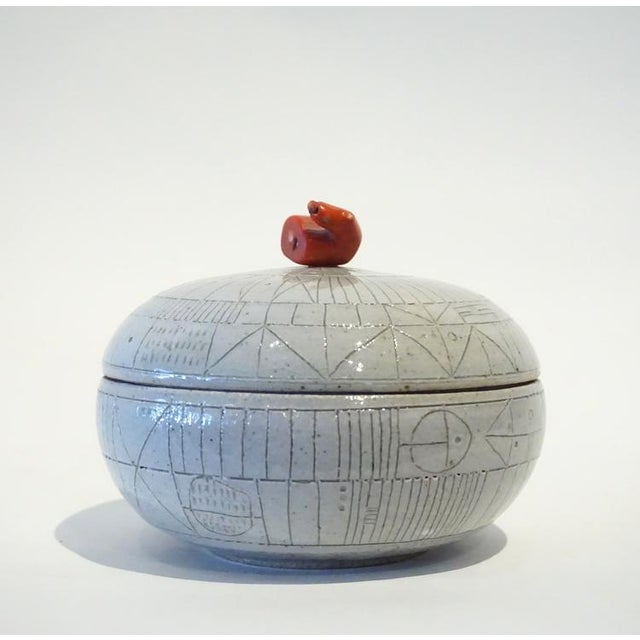 This pale gray ceramic, scribed box features a lid with a coral finial. By Studio potter, Heather Rosenman, circa 2016....