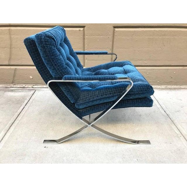 Pair of chrome lounge chairs. Has blue velvet upholstery.