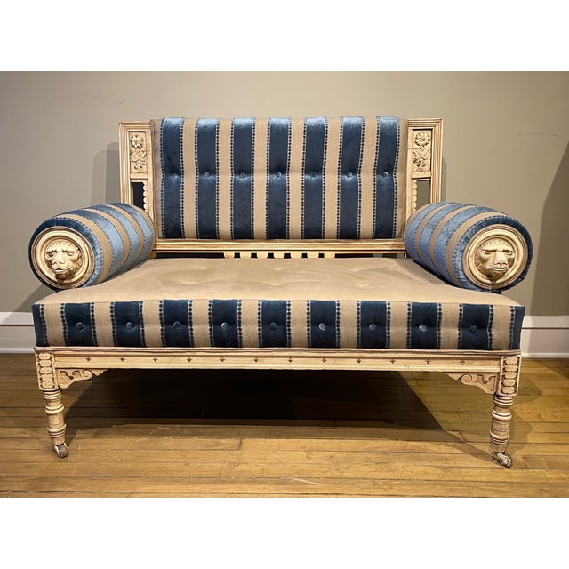 Mid 19th century settee with decorative lion head medallions in the arms. The wood frame has a beautiful patina and is...