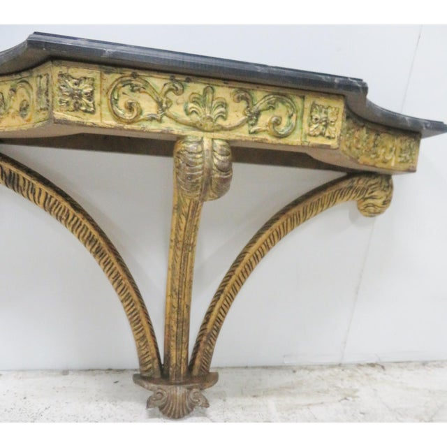 Gilt carved plumes under a faux painted marble top.
