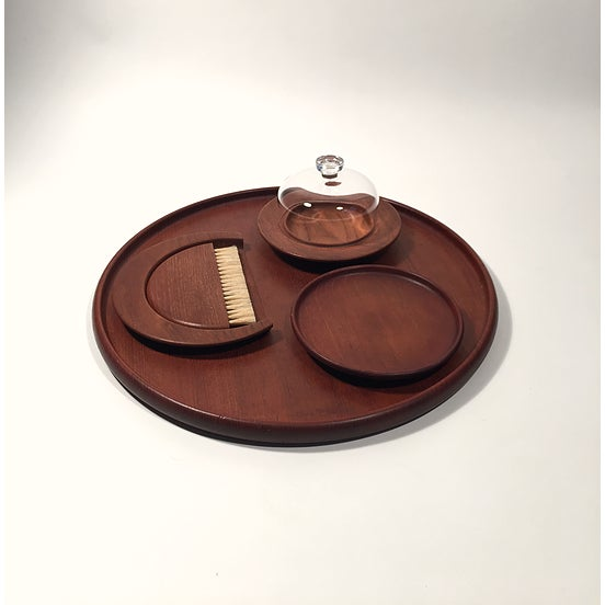 Collection of teak table accessories all by Kay Bojesen including: crumber/brush, large round tray, small round plate,...