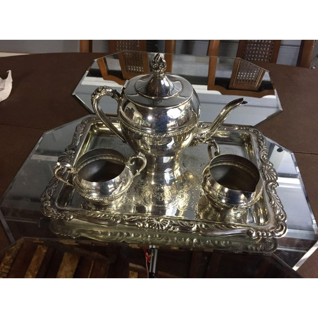 """Three-piece silver-plate tea set with engraved designs. Display maker's mark on the tray and tea pot Sugar pot, 2 3/4"""" Top..."""