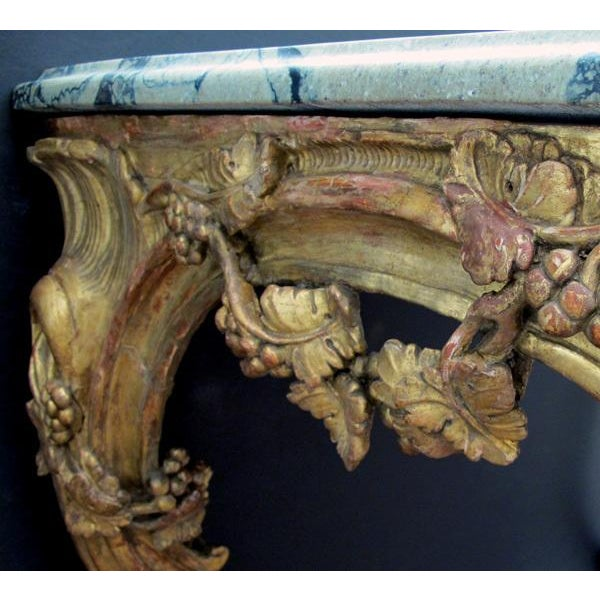 A curvaceous and finely carved Venetian rococo giltwood console table with grape vine motif and sage green marble top; the...