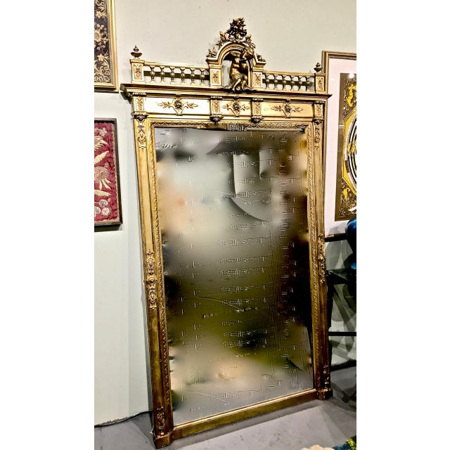 This is an impressive c. 1870-1880 French pier or over-mantle mirror that is surmounted by a well-carved and gilt putti....