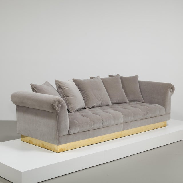 A Large Deep Buttoned Soft Grey Cotton Velvet Upholstered Sofa on a Polished Brass Base created by Talisman Bespoke. This...