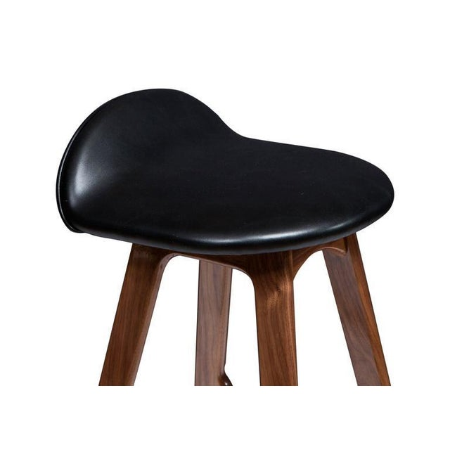 """Boyd stool shown in solid walnut with black leather seat. Seat Height -29.75"""" Custom orders have a lead time of 2-8 weeks..."""