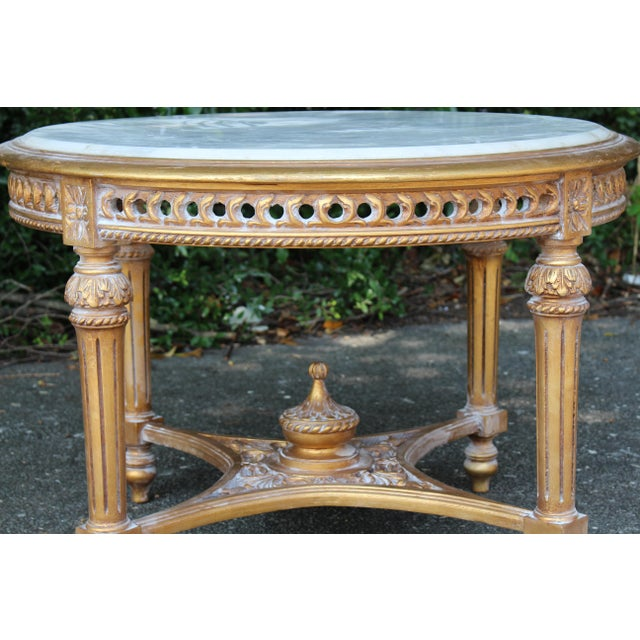 Louis XVI style antique table with Carrara marble insert. The new gold leaf finish showcases the hand-carved gilt trim,...