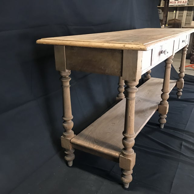 A versatile long narrow rustic French scrubbed pine sofa table, sideboard or credenza with antique ceramic pulls, circa...