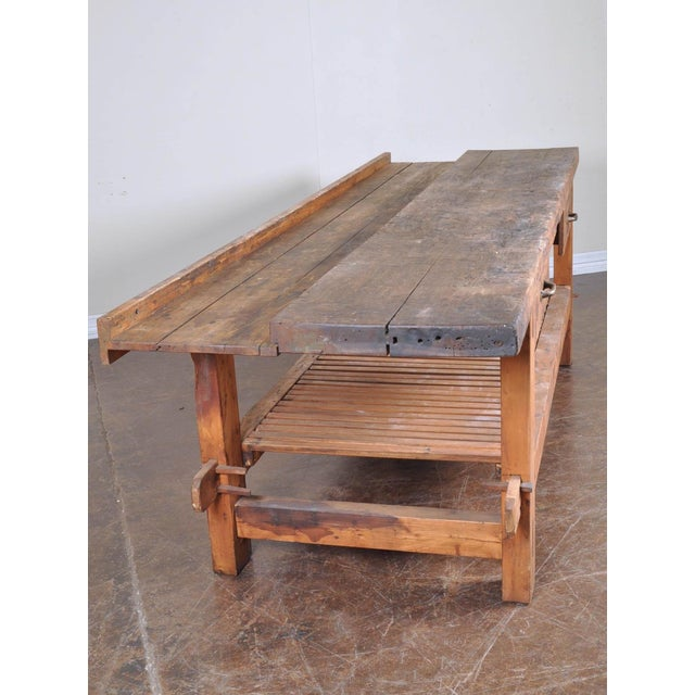 A wonderfully rough antique vintage French industrial solid workbench. This has two functional drawers and a trough built...