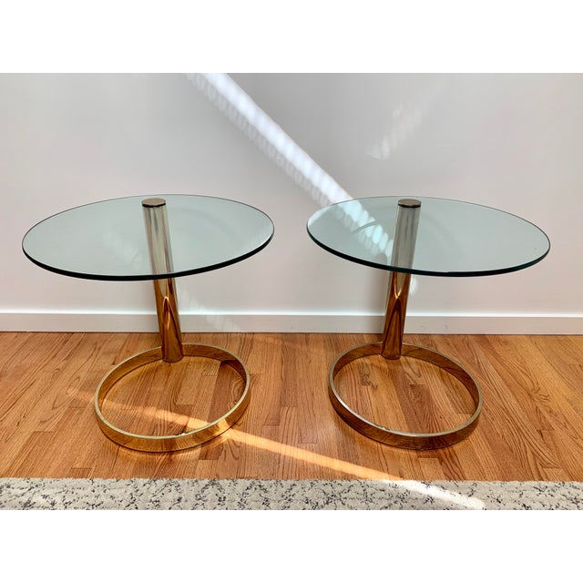 Striking pair of side tables feature a brass finish metal column rising from an open circular base supporting a thick...