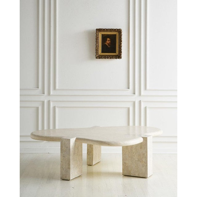 A statement tessellated stone coffee table featuring an amoebic shaped top that is supported by three rectangular column...