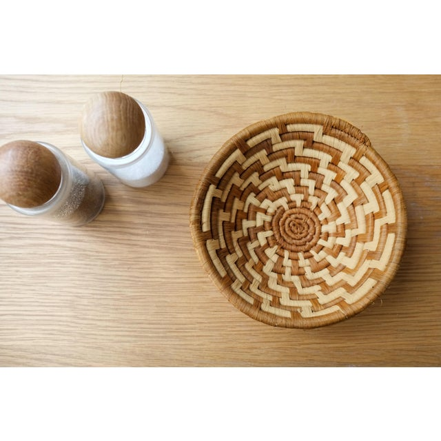 Mini handwoven African raffia basket bowl with cognac and sandy mustard hues. Paired with white oak and our grey Koik...