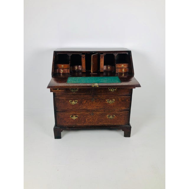 A handsome and rustic early Georgian oak slant front desk made in England during the first half of the 18th century. The...