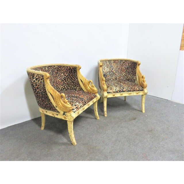 Quality pair of French swan carved Bergeres. Cream and gold gilt finish, leopard print upholstery.