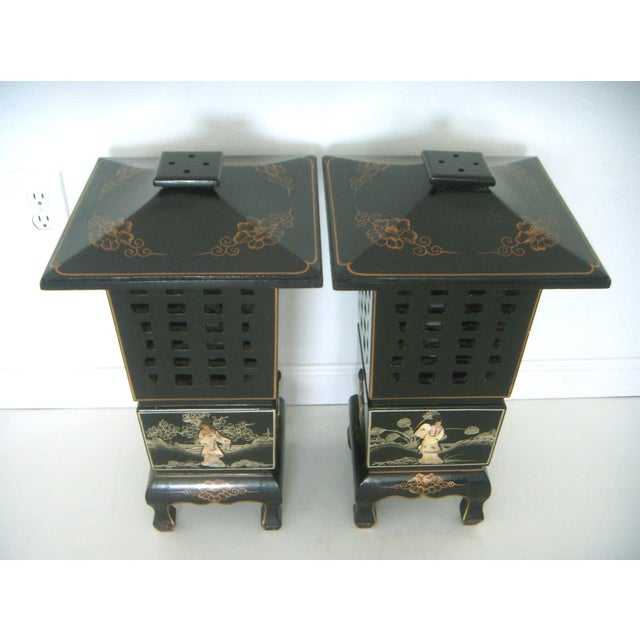 An unusual pair of vintage Chinese style black lacquer lamps/lanterns. Each hand crafted lamp has cut out decorative upper...
