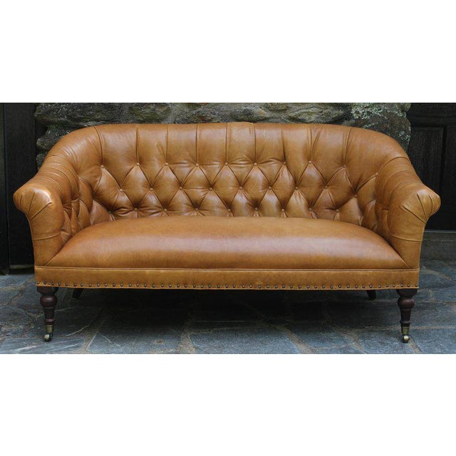 A small-scale Edwardian style buttoned back sofa upholstered in a supple caramel colored leather hide accented with brass...