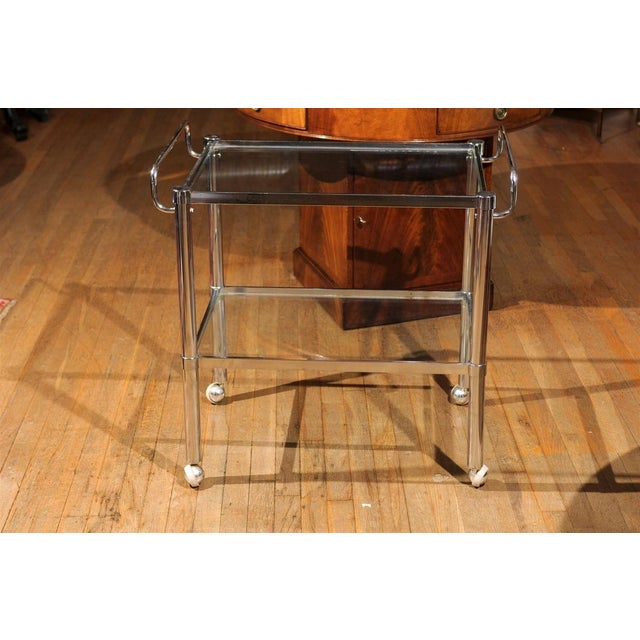 Mid-Century bar cart of chrome having two tiers holding glass panels and upturned handles on either side. The cart is...