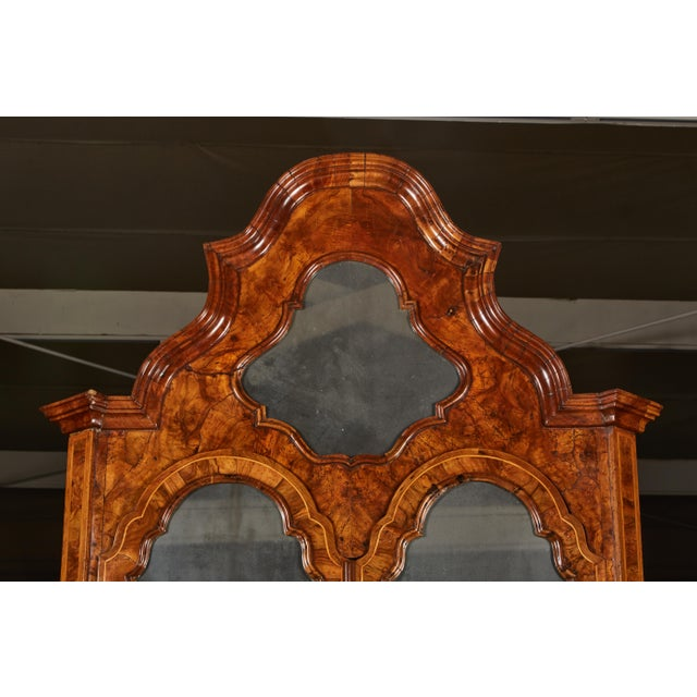 The veneered secrétaire in two parts: The upper section with an arched cornice containing a mirror, over two doors that...
