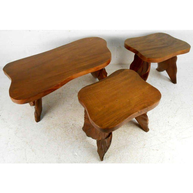 This 1970s walnut table set includes a coffee table and pair of side tables, all featuring matching hand-carved legs. Wear...