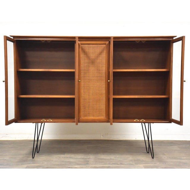 A mid century modern walnut bookcase with a fixed cane center, four glass doors, brass knobs, two fixed shelves, and black...