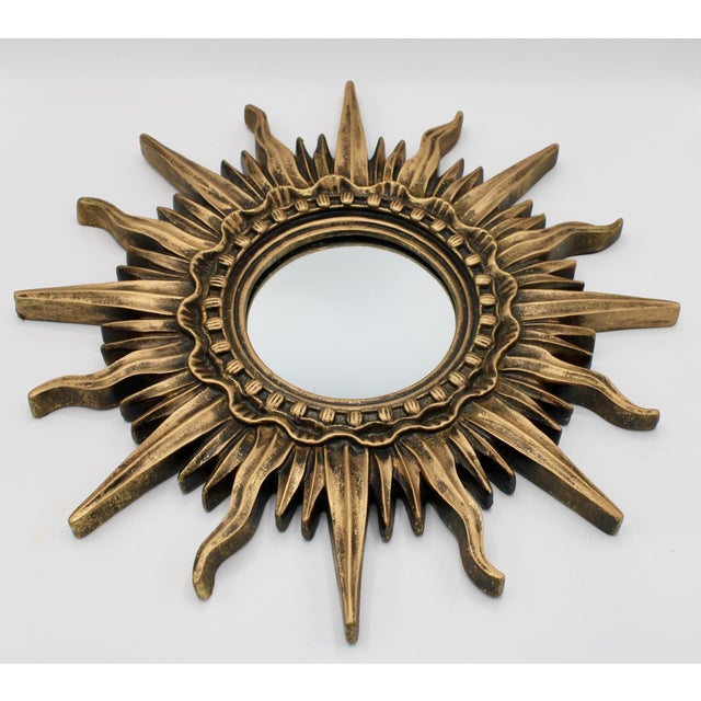 A radiant French Gold Sunburst Mirror, circa 1930. New mirrored glass. Comes ready to hang. This French sunburst mirror is...