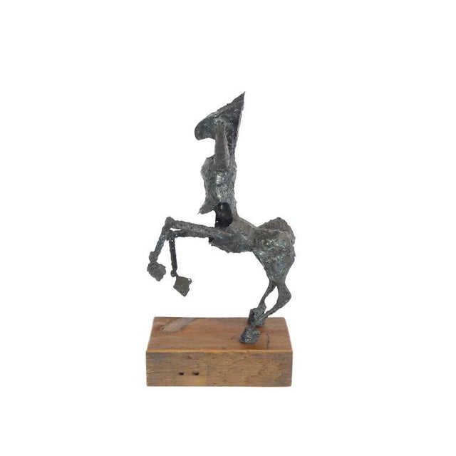 This is an abstract steel sculpture of a centaur mounted on a wood base.