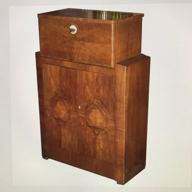 Wooden liquor bar by Sidney Lyons. Features a top drawer and center cache with apertures for bottle placement. Marked:...