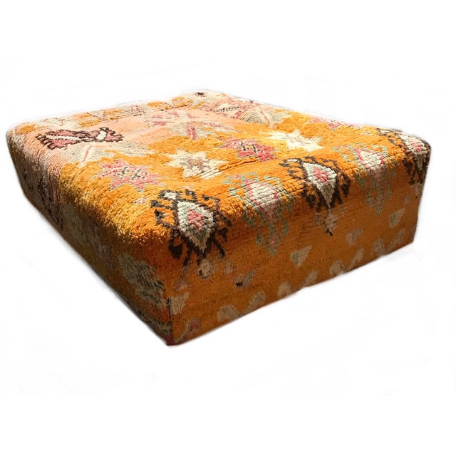 A fantastic vintage ottoman, upholstered with the fragment of an antique tribal rug, circa 1900. The rug has gorgeous,...