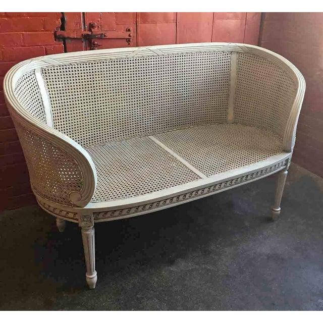 Late 20th century classic French style settee. Made in Indonesia for export. Double caned seat and back with mahogany...