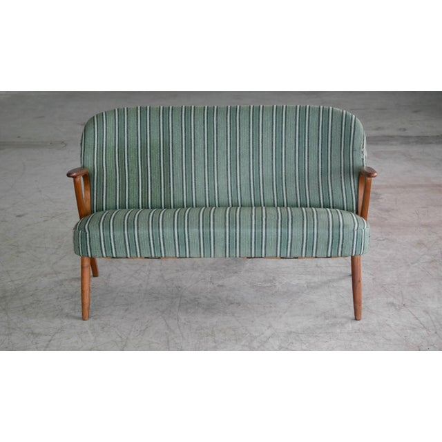 Beautiful and elegant small 1950s Danish sofa with legs and armrests in teak. The high quality woodwork and design is very...