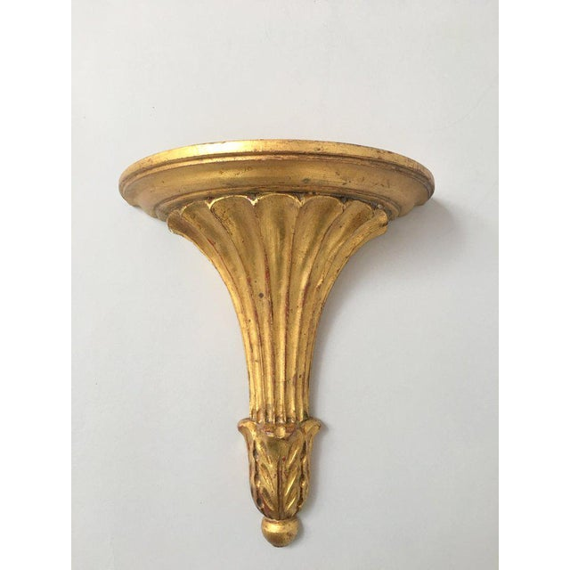 Italian gilt wood wall shelf / sconce / bracket shelf. The shelf features a fluted neck with stylized acanthus leaves atop...