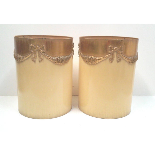 Ornate Regency ivory lamp shades in a tall, cylindrical form adorned with gilt faux ormolu ribbon bows and rose swags....