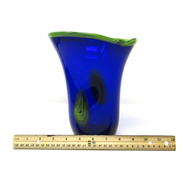A gorgeous hand-blown cobalt blue art glass vase with yellow trim. The glass is thick and heavy relative to the vase's...
