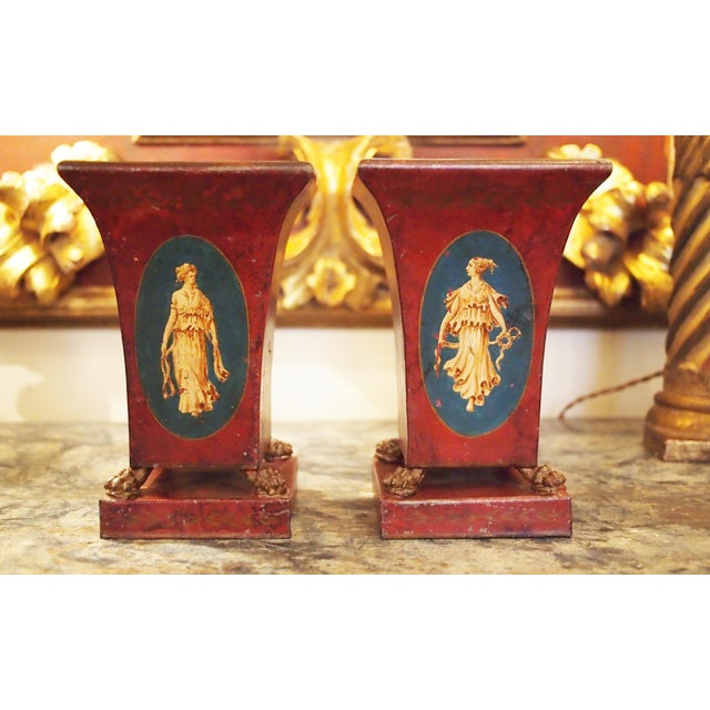 A pair of tole vases, each with liners, the vases flared and on paw feet resting on a square base. The red painted vases...