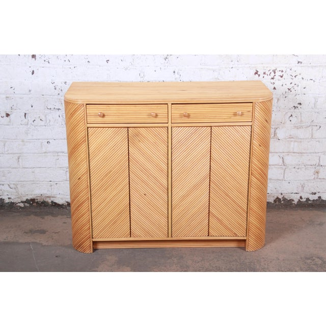 An exceptional mid-century Hollywood Regency split reed rattan compact sideboard cabinet In the manner of Gabriella Crespi...