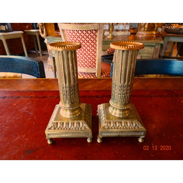 Pair of French 19th Century bronze fluted candle holders on a square base with four finials underneath. Circa 1850.