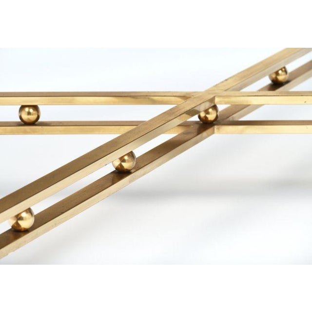 Italian modernist coffee table made of black lacquered steel and gilt brass. The piece has an x stretcher connecting four...