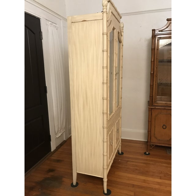 This fabulous Thomasville piece has an amazing silhouette with a pagoda top , fretwork and faux bamboo wood details. There...