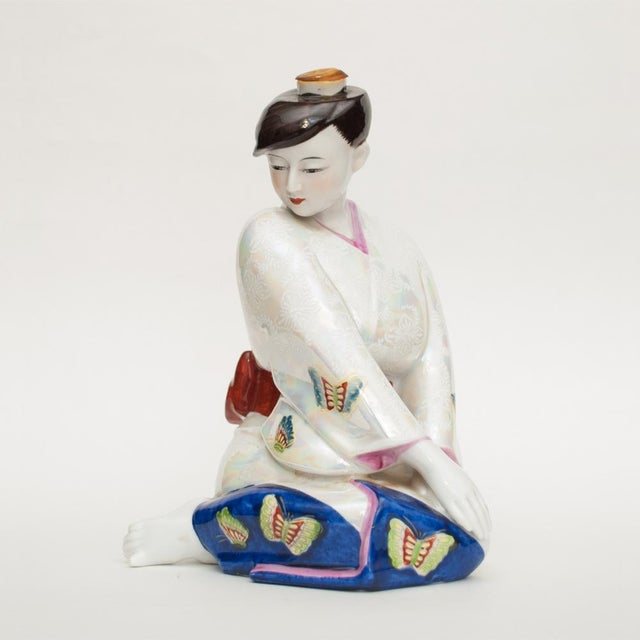 A beautiful vintage Japanese porcelain sake bottle in a shape of seated barefoot girl wearing kimono decorated with...