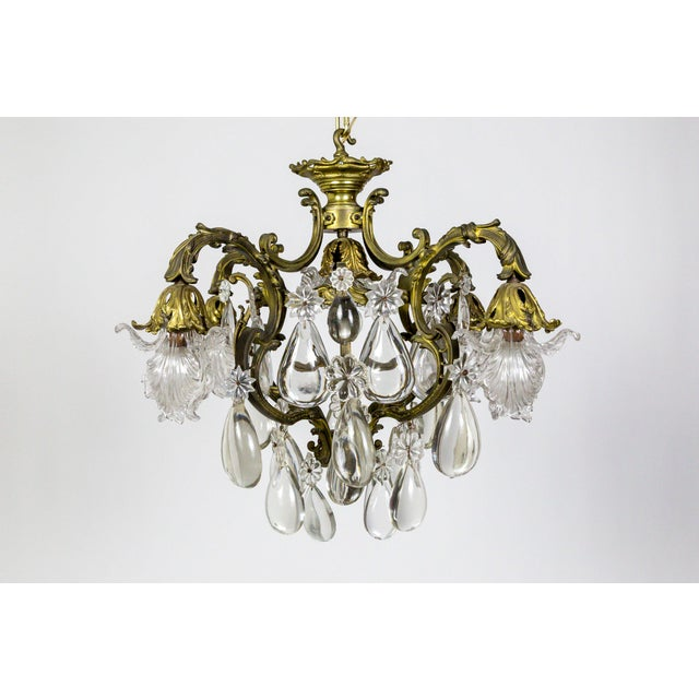 A mesmerizing, French, Belle Epoch, 5-light, heavy bronze chandelier with major smooth, half-back, almond, crystals and...